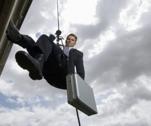Businessman Rappelling Down By Rope