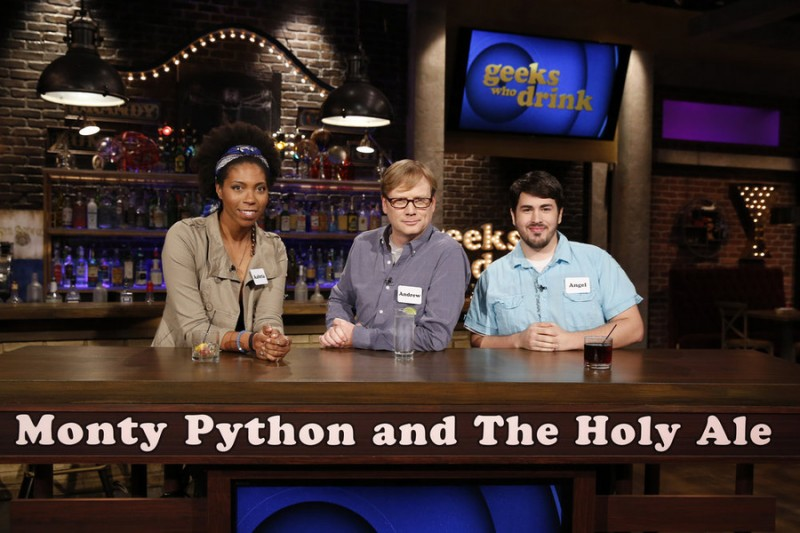 "GEEKS WHO DRINK -- ""Matthew McCaull VS. Andrew Daly"" Episode 101 -- Pictured: (l-r) Aabria Lipscomb, Andrew Daly, Angel Castillo -- (Photo by: Carol Kaelson/Syfy)"