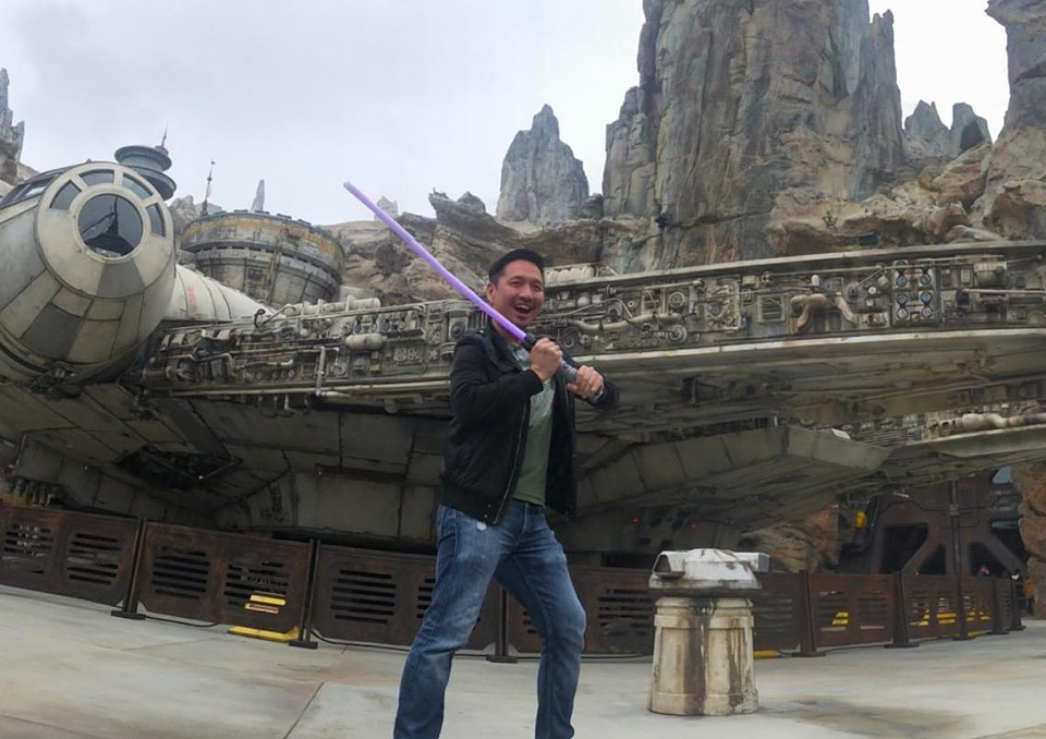Nerd Reactor's John Nguyen wielding a lightsaber at Star Wars: Galaxy's Edge. Credit: Hanae Cajigas / Nerd Reactor