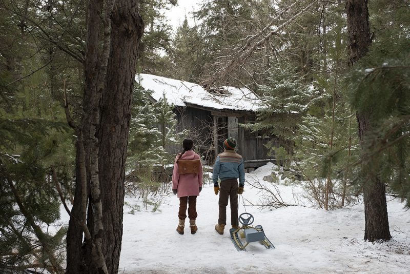 Tales from the Loop - Two kids stand in front of a cabin